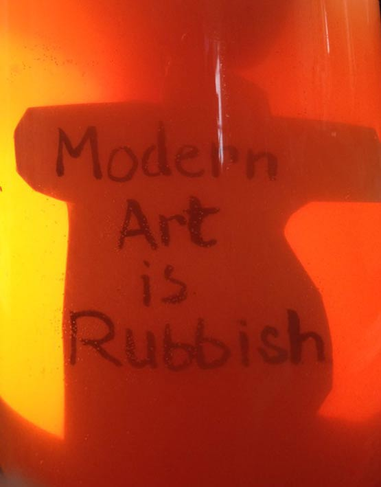 Modern art is rubbish written on card that looks like it is submerged in Orange Urine